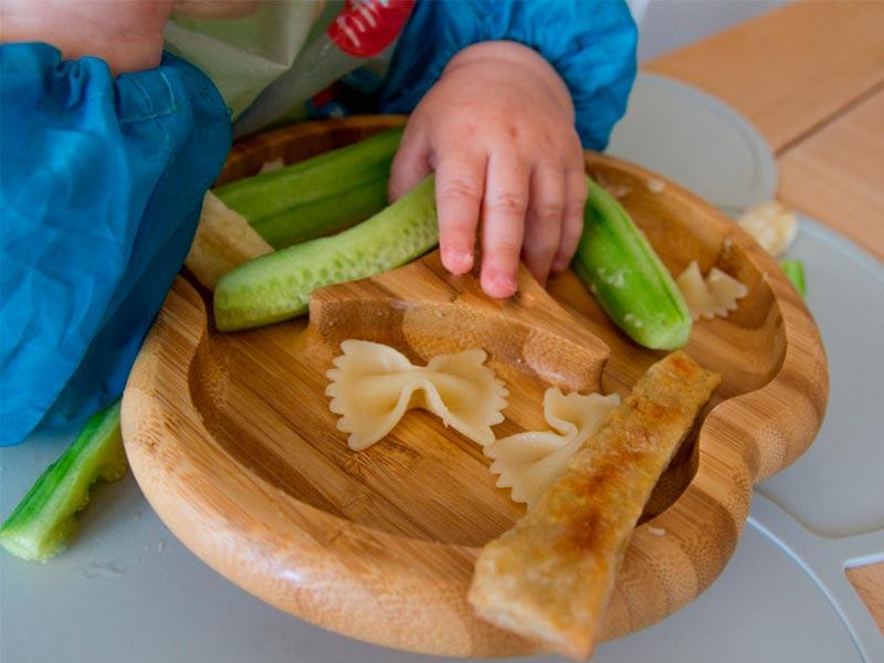 bebe comiendo pepino en plato de bambu